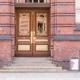 Brown and gold doorway set in brick building