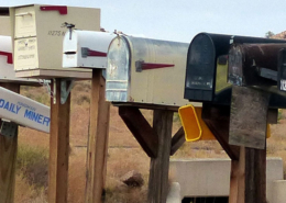Mailboxes of various size, shape, and color in a long row