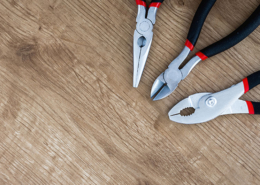 Pliers and snippers on a wood background
