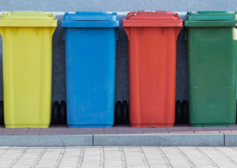 Four colorful recycling bins on a curb